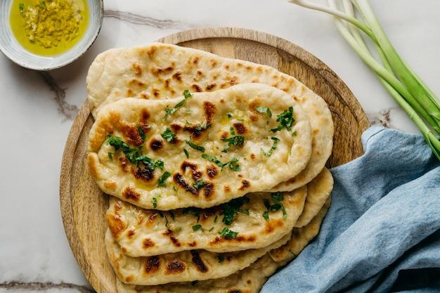 Comida paquistanesa na vista superior de uma placa de madeira