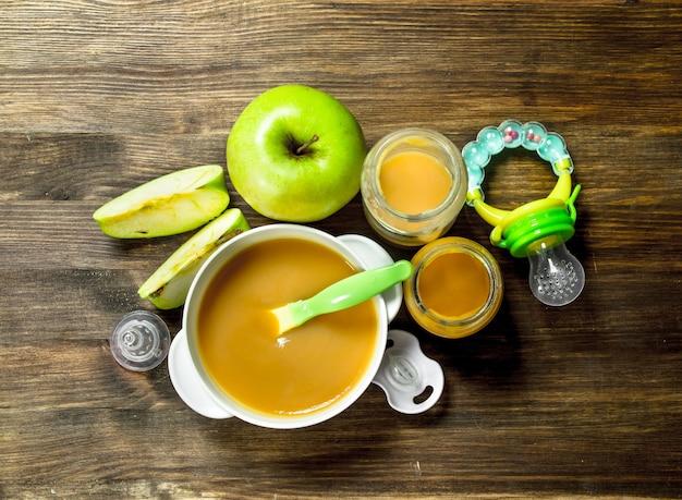 Comida para bebê bebé purê de maçãs verdes em um fundo de madeira