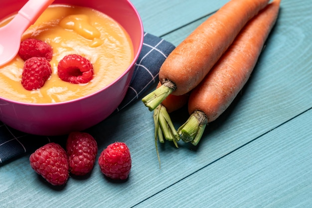 Comida para bebê com framboesas e cenouras em ângulo alto