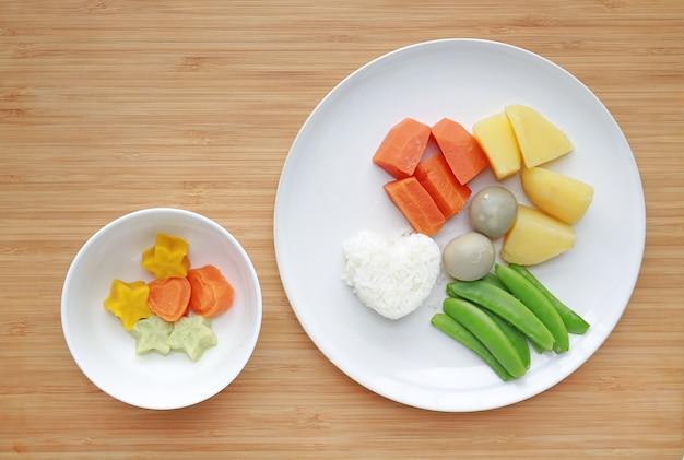 Comida para bebé cozida (cenoura, ovo, batata, arroz e ervilha) com puré de papa congelado