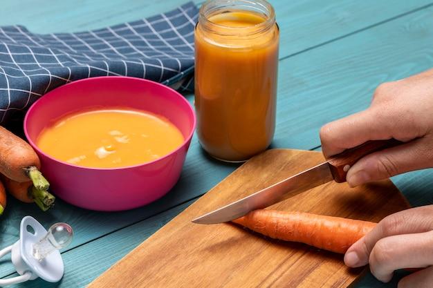 Comida para bebê de ângulo alto com cenoura e chupeta