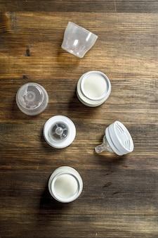 Comida para bebé leite para bebé em pequenos frascos sobre uma mesa de madeira