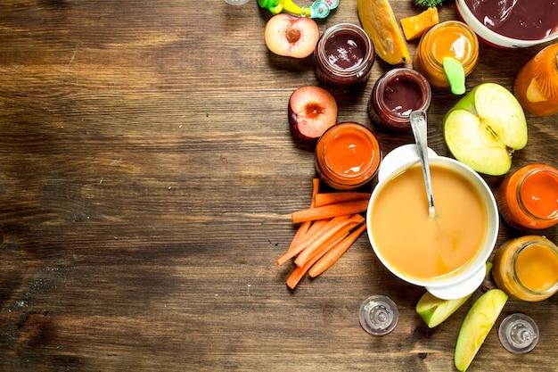 Comida para bebê vários purês de frutas e vegetais em um fundo de madeira