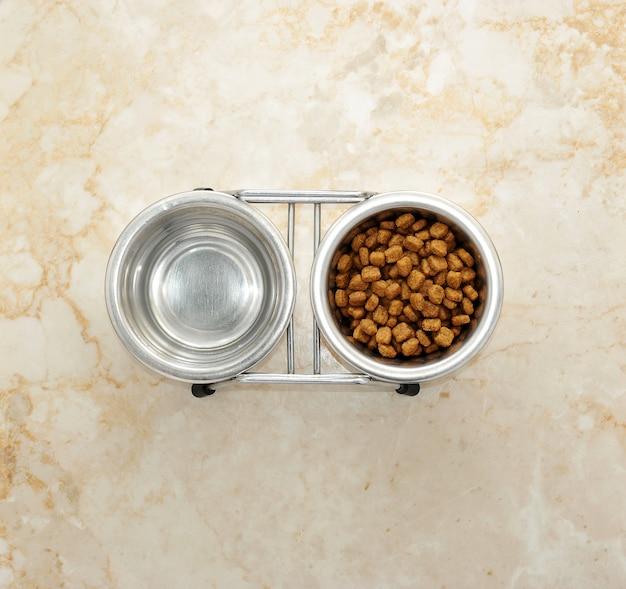 Comida para cachorro e água em tigelas de metal