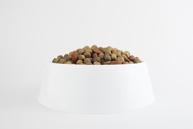 Comida para cachorro ou gato. ração seca para gatinhos ou filhotes de perto em uma tigela branca sobre um fundo branco