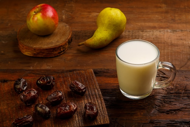 Comida para iftar no sagrado ramadã em uma mesa de madeira com tâmaras, frutas e ayran