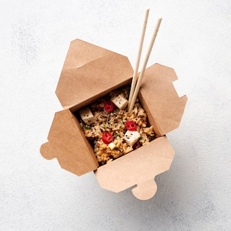 Comida para levar plana de arroz e legumes com pauzinhos