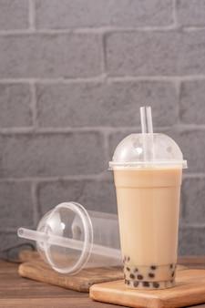 Comida para viagem com conceito de item descartável popular taiwan bebida bolha leite chá com copo de plástico e canudo na mesa de madeira