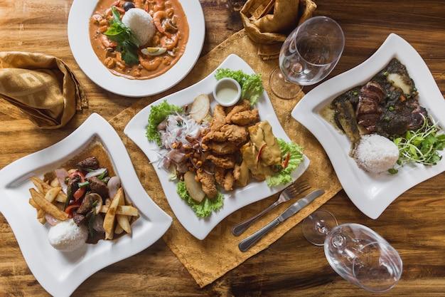 Comida peruana, ceviche, lomo saltado, piqueo em uma elegante mesa de restaurante