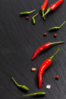 Comida picante apresentação fundo vermelho pimentão e pimentão verde na placa de ardósia preta