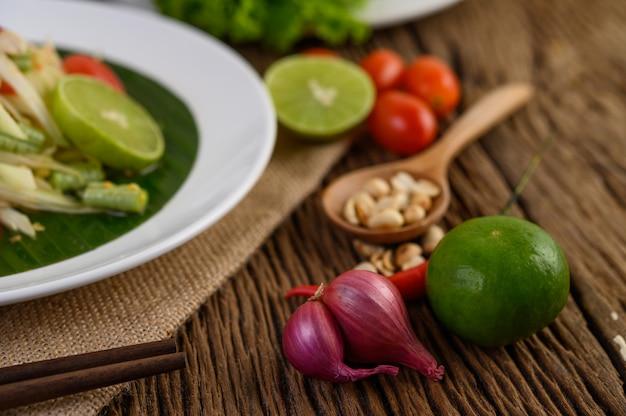 Comida picante de estilo tailandês, conceito de comida som tum, decoração de adereços alho, limão, amendoim, tomate e cebolinha na mesa de madeira