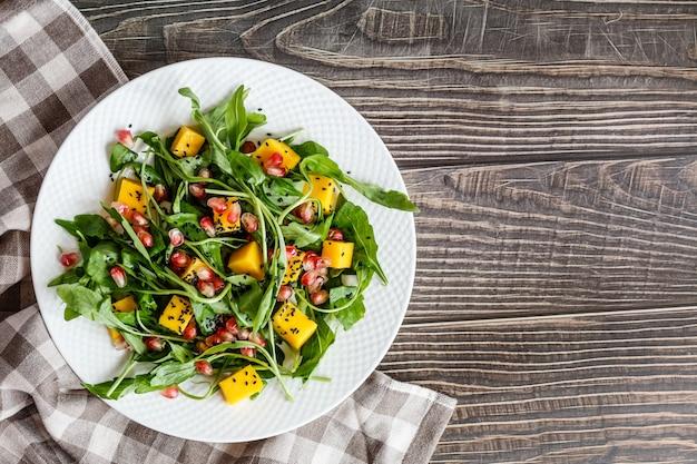 Comida plana leigos. vista do topo. salada com manga, abóbora assada, rúcula, sementes de romã deitado na chapa branca