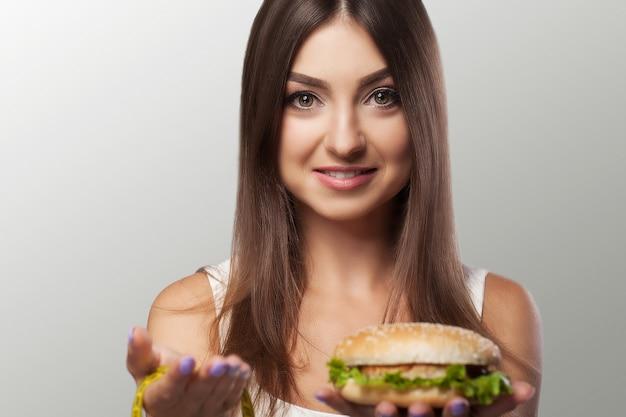 Comida prejudicial. a escolha entre comida maliciosa e esporte. linda garota de dieta. o conceito de beleza e saúde.