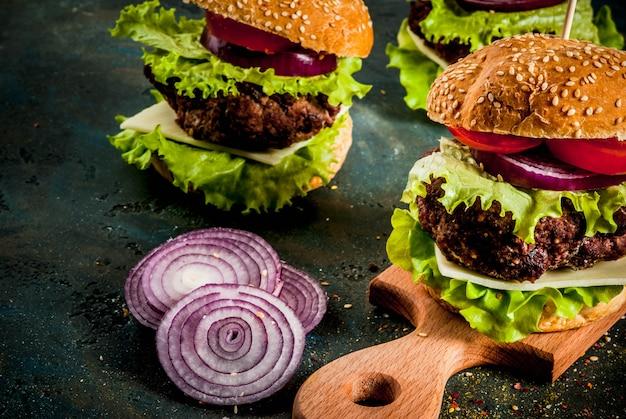 Comida rápida. alimentos não saudáveis. deliciosos hambúrgueres saborosos frescos com costoleta de carne, legumes frescos e queijo em concreto azul escuro. copyspace