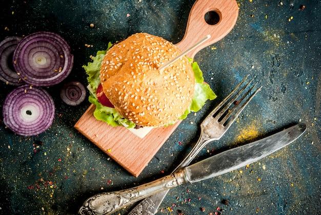 Comida rápida. alimentos não saudáveis. deliciosos hambúrgueres saborosos frescos com costoleta de carne, legumes frescos e queijo em concreto azul escuro. vista superior copyspace