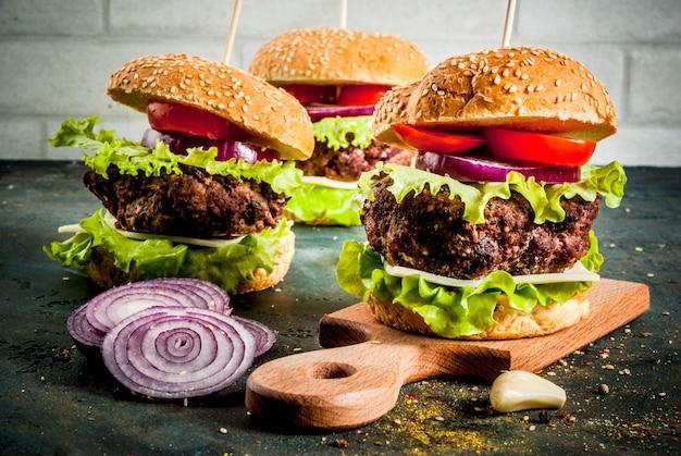 Comida rápida. alimentos não saudáveis. deliciosos hambúrgueres saborosos frescos com costoleta de carne, legumes frescos e queijo em concreto azul escuro.