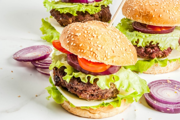 Comida rápida. alimentos não saudáveis. deliciosos hambúrgueres saborosos frescos com legumes frescos e queijo de costeleta de carne no fundo branco