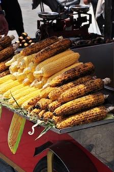 Comida rápida. espigas de milho fritas e frescas. balcão de quiosque de fast food.