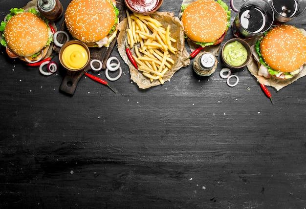 Comida rápida. hambúrgueres com batata frita e coca-cola. no quadro negro.