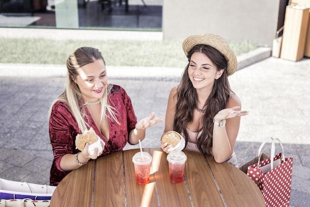 Comida rápida. mulheres positivas e felizes sentadas juntas à mesa enquanto comem hambúrgueres no café