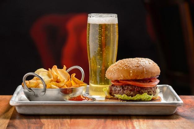 Comida rápida. um grande hambúrguer com carne e um copo de cerveja.