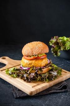 Comida rápida. um grande hambúrguer e sobre um fundo escuro.