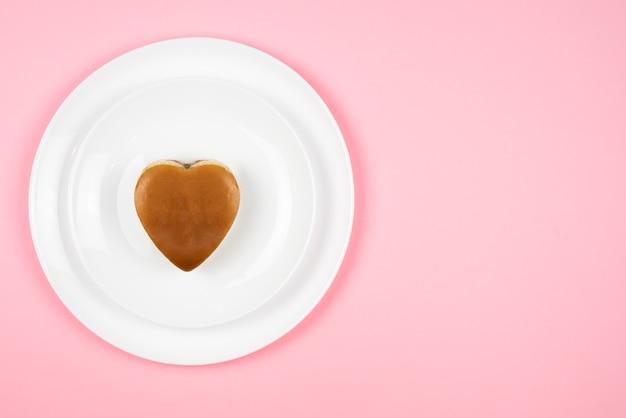 Comida rápida. um hambúrguer em forma de coração num prato branco. . comida para o dia dos namorados.
