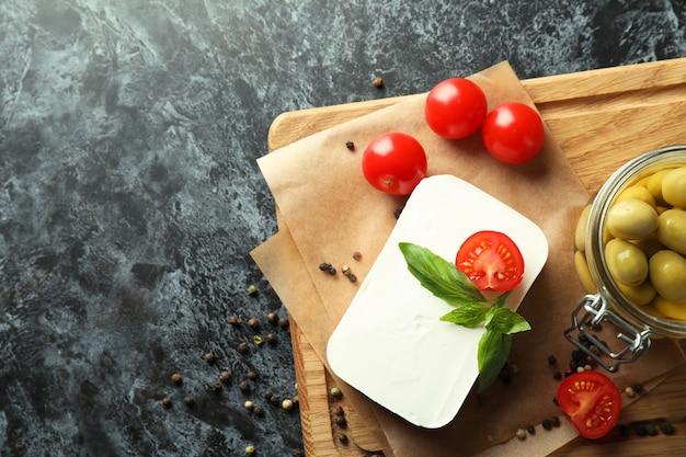 Comida saborosa com queijo feta em superfície preta esfumada