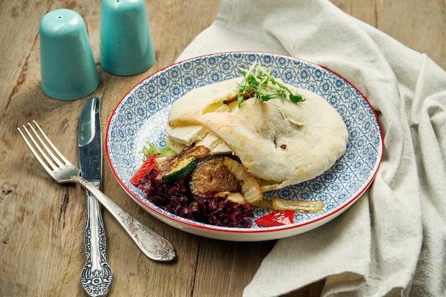 Comida saborosa de rua - pão árabe com tomate, pepino em blate azul na mesa de madeira. cozinha grega. feche acima da vista. shwarma