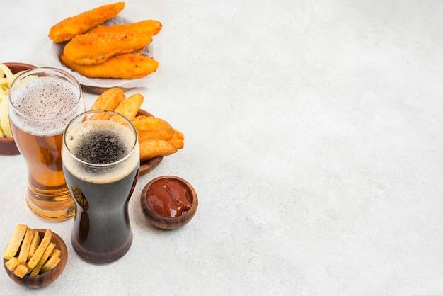 Comida saborosa e copos de cerveja com cópia-espaço