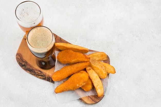 Comida saborosa e copos de cerveja de alto ângulo