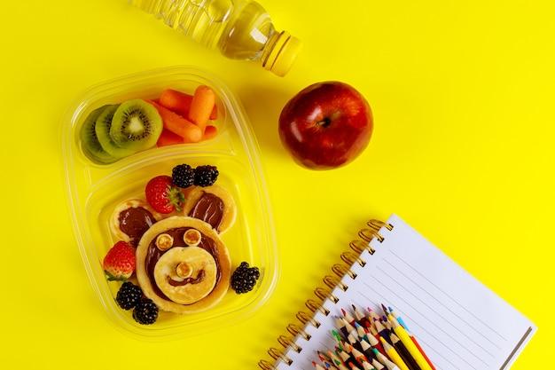 Comida saborosa em recipiente e lápis coloridos na superfície amarela