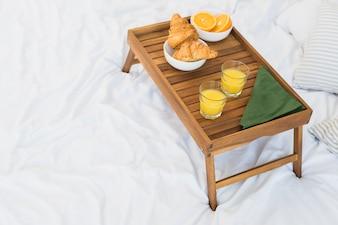 Comida saborosa na mesa de café da manhã na folha de cama branca