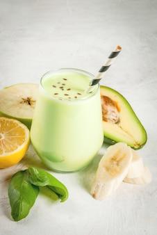 Comida saudável. café da manhã ou lanche dietético. smoothies verdes de iogurte, abacate, banana, maçã, espinafre e limão. na mesa de pedra branca de concreto, com ingredientes. copyspace