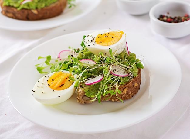 Comida saudável. café da manhã. sanduíche de ovo de abacate com pão integral na superfície de madeira branca.