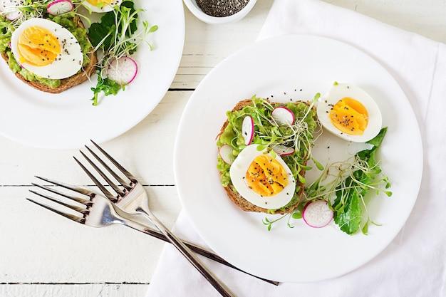 Comida saudável. café da manhã. sanduíche do ovo do abacate com pão inteiro da grão no fundo de madeira branco. vista do topo. lay plana