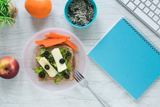 Comida saudável com livro espiral e teclado de computador sem fio na mesa