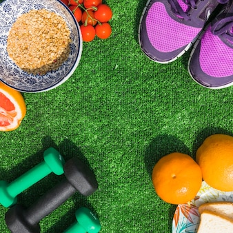 Comida saudável com par de sapatos de desporto e halteres no relvado
