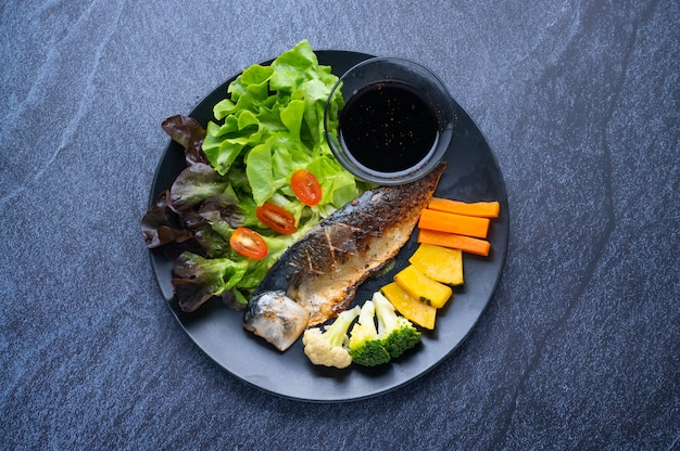Comida saudável, composta por peixe grelhado, variedade de legumes, ervas e molho japonês