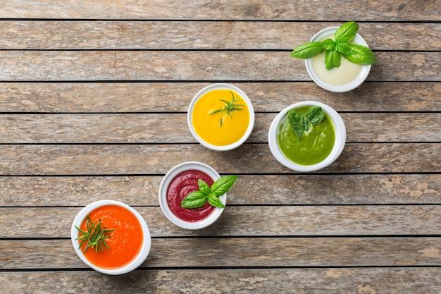 Comida saudável, conceito de alimentação limpa. variedade de sopas cremosas de vegetais coloridos sazonais de outono com ingredientes. abóbora, brócolis, cenoura, beterraba, batata, espinafre de tomate. postura plana, copie o espaço