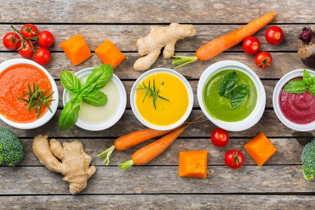 Comida saudável, conceito de alimentação limpa. variedade de sopas cremosas de vegetais coloridos sazonais de outono com ingredientes. abóbora, brócolis, cenoura, beterraba, batata, espinafre de tomate. postura plana