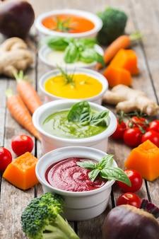 Comida saudável, conceito de alimentação limpa. variedade de sopas cremosas de vegetais coloridos sazonais de outono com ingredientes. abóbora, brócolis, cenoura, beterraba, batata, tomate, espinafre