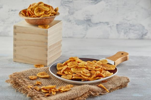 Comida saudável de chips de banana, frutas secas e chips de vegetais saudáveis, lanches vegan saudáveis na serapilheira em um prato e carrinho de madeira.
