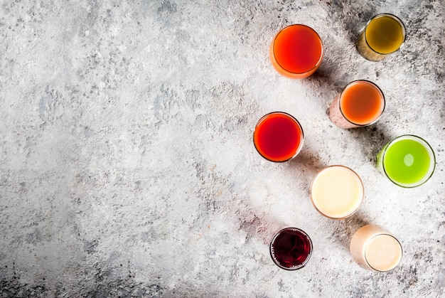 Comida saudável, diferentes frutas e legumes sucos smoothie em copos vista superior copyspace