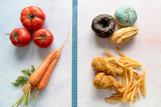 Comida saudável e alimentos pouco saudáveis divididos de fita de medição