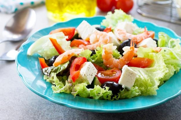 Comida saudável e dietética salada grega com camarão e vegetais em uma mesa leve de pedra ou ardósia