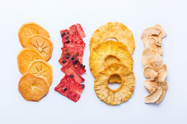 Comida saudável e equilibrada, alimentação limpa, lanches com sabor natural, conceito de ingredientes transparentes. frutas secas, caqui desidratado, melancia, abacaxi, chips de maçã em um fundo branco
