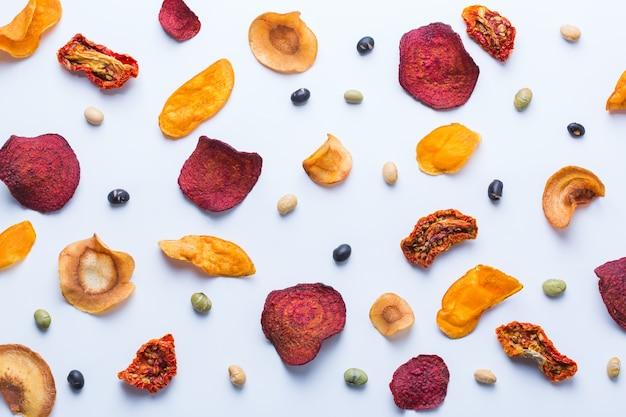 Comida saudável e equilibrada, alimentação limpa, lanches com sabor natural, conceito de ingredientes transparentes. legumes secos, batata-doce desidratada, pastinaga, chips de beterraba em um fundo branco