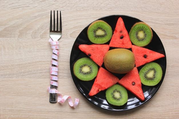 Comida saudável e fita métrica na mesa de madeira, conceito de dieta