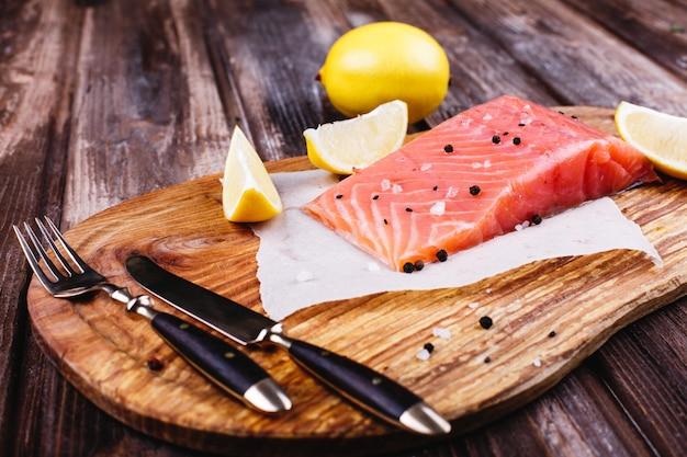 Comida saudável e fresca. salmão cru servido com limões e facas na placa de madeira